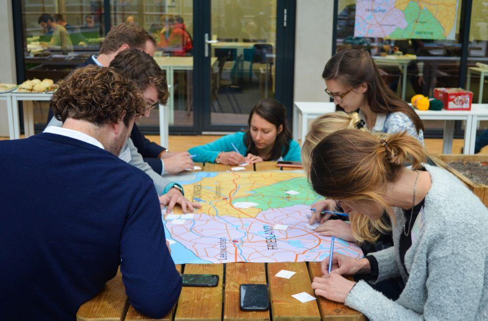 Jongeren rondom een landkaart
