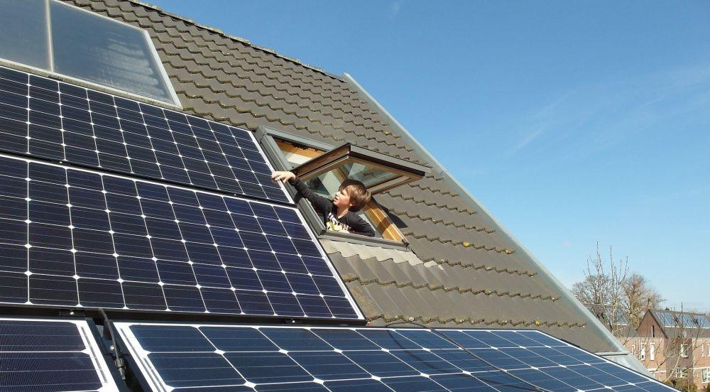 Zonnepanelen op dak met kind in dakraam